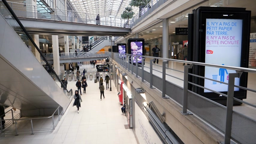 dojíždění : PARIS, FRANCE - CIRCA 2019: Cold tones footage of slow motion scene of Gare du Nord interior with large group of computers walking to catch the RER metro Eurostar trains - advertising boards and elevators in one of the most frequented train station in Par