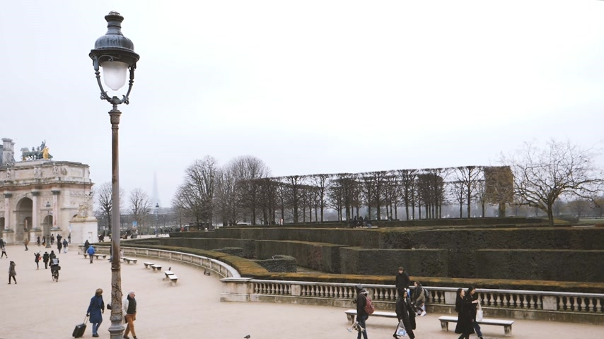 сосредоточиться на переднем плане : Paris, France - Circa 2019: Elevated view of tourists and locals walking in the Jardin des Tuileries With Eiffel Tower in background covered with mist. View from Place du Carousel Стоковые видеозаписи