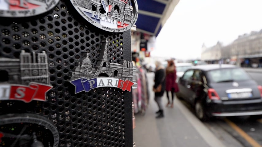 eifel : PARIS, FRANCE - CIRCA 2019: Slow motion footage of pedestrians walking near souvenir shop with Eiffel Tower magnets on the magic Parisian Quai St Michel a few meters from Notre-Dame of the touristy street Stock Footage