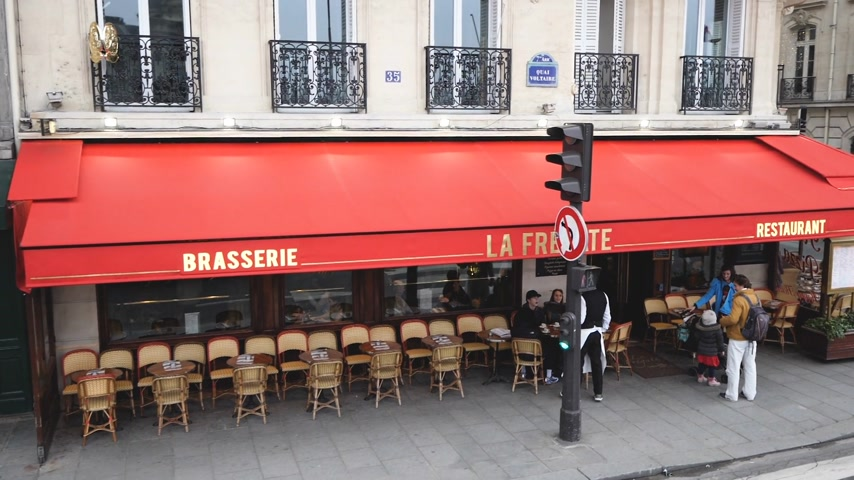 markiza : PARIS, FRANCE - CIRCA 2019: Angle Quai Voltaire elevated view aerial drone over Parisian street with crowded Cafe la Fregate - pedestrians walking and beautiful Haussmannian architecture buildings slow motion waiter taking order at terrace