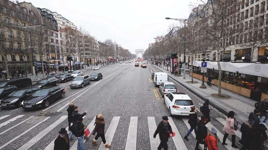 champs elysee : Paris, France - Circa 2018: Slow Motion pedestrians crossing street at green light in central Paris on the iconic Champs Elysee boulevard avenue with Triumphal arch in the background