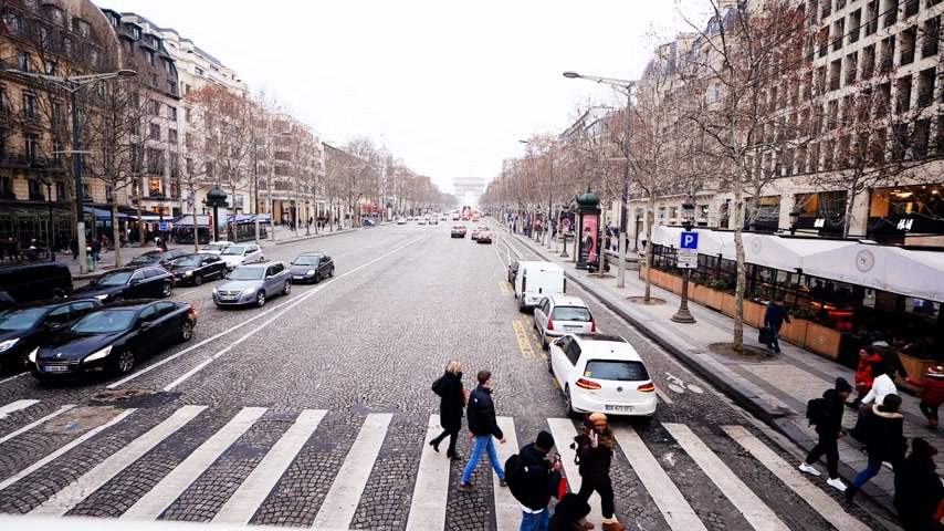 oblouk : Paris, France - Circa 2018: Cinematic color grading over slow Motion pedestrians crossing street at green light in central Paris on the iconic Champs Elysee boulevard avenue - aerial view with Arc de Triomphe in the background Dostupné videozáznamy