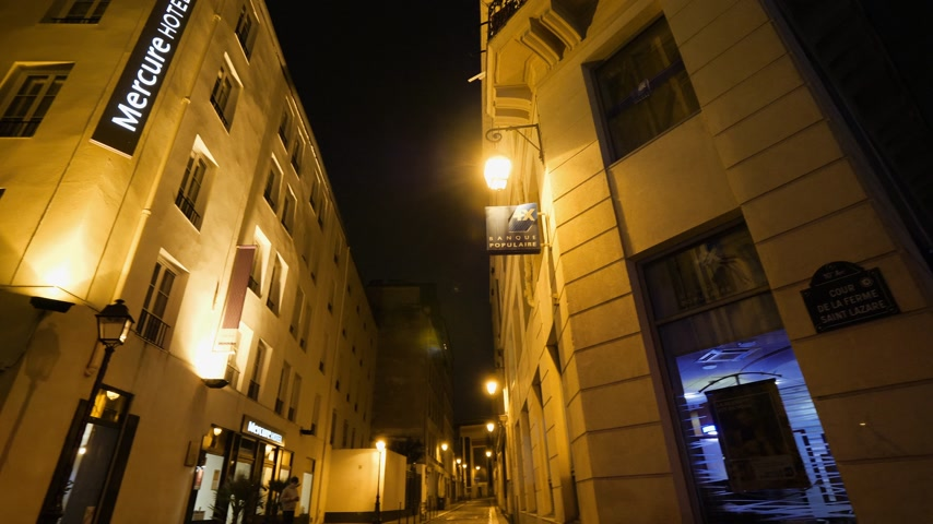 onarılmış : Paris, France - Circa 2019: Accor Mercure Paris Gare de lEst Magenta hotel pan with perspective over tiny French street at night Stok Video