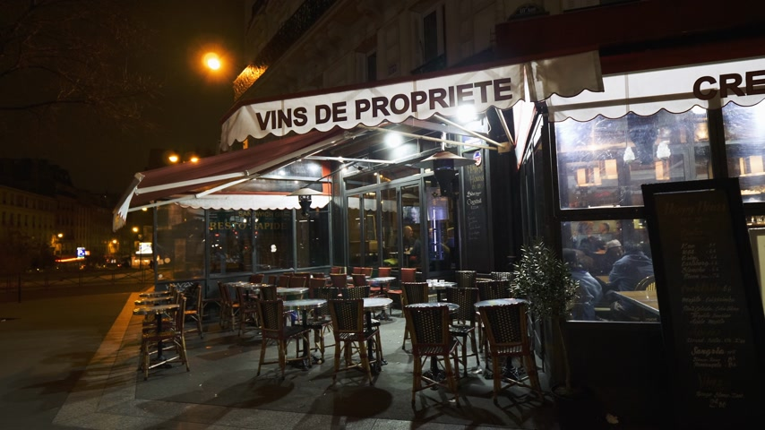 cena urbana : PARIS, FRANCE - CIRCA 2018: Le Prevoyant typically French restaurant with empty street terrace on Boulevard de Magenta at night. Selling French wines Vins de propriete