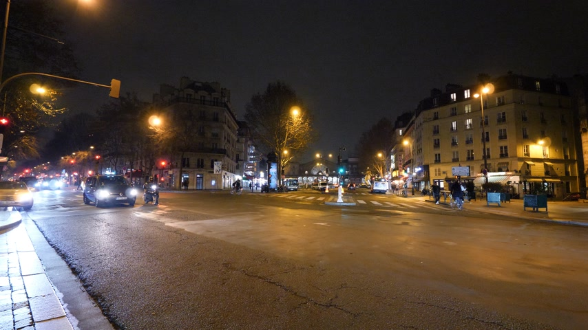 macskaköves : Paris, France - Circa 2019: Iridescent light radiating beam light coming from street lights buildings and people on Paris street at dusk - conceptual pandemic situation in European capital Stock mozgókép