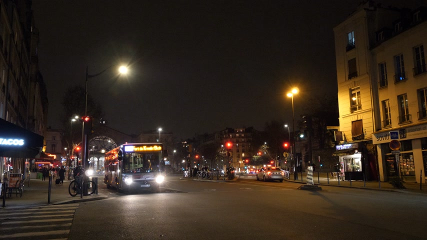 eski şehir : PARIS, FRANCE - CIRCA 2019: Parisian street Rue du Faubourg Saint-Martin at night near Gare de Est train station with empty bus driving, cars, taxis Stok Video