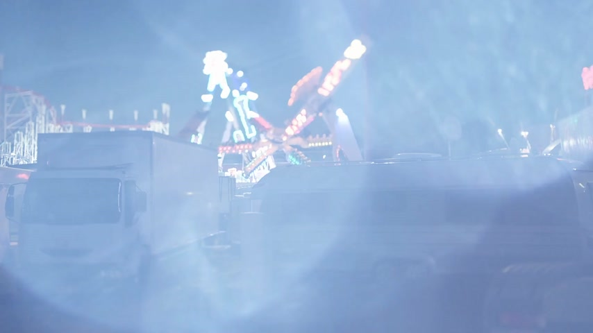 tilt : Strasbourg, France - Circa 2018: Tilt-shift lens footage with night scene of amusement park with parked white trucks and Ferris wheel merry-go-round spinning in the background at dusk - cinematic flare