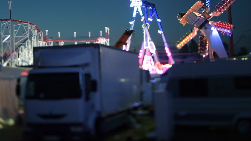 tilt shift : Cinematic 4k UHD night scene of amusement park with parked white truck, trailer, roller coaster and Ferris wheel merry-go-round spinning in the background at dusk