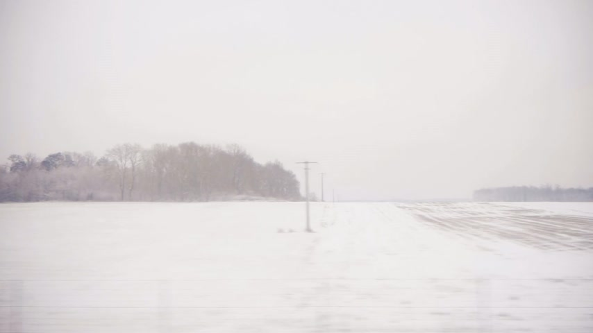 sepya : Winter scenery seen from the in motion train - French landscape with cold weather - slow motion with trees covered with snow, villages and roads cinematic sepia color Stok Video