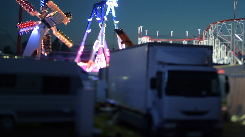 tilt shift : Night scene of amusement park with parked white truck, trailer, roller coaster and Ferris wheel merry-go-round spinning in the background at dusk Stock Footage
