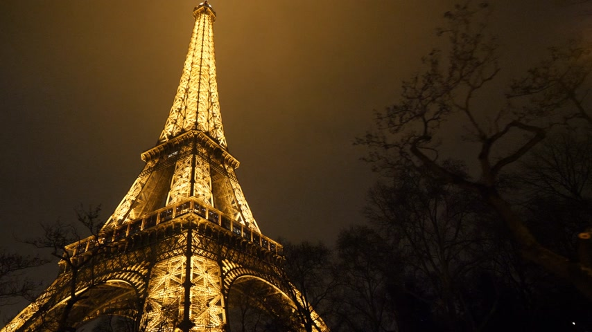 ave : PARIS, FRANCE - JAN 2019: Steadicam approaching illuminated majestic Eiffel Tower down to top view in Paris - the most visited monument in France being lit sightseeing discovering the French capital Stock Footage