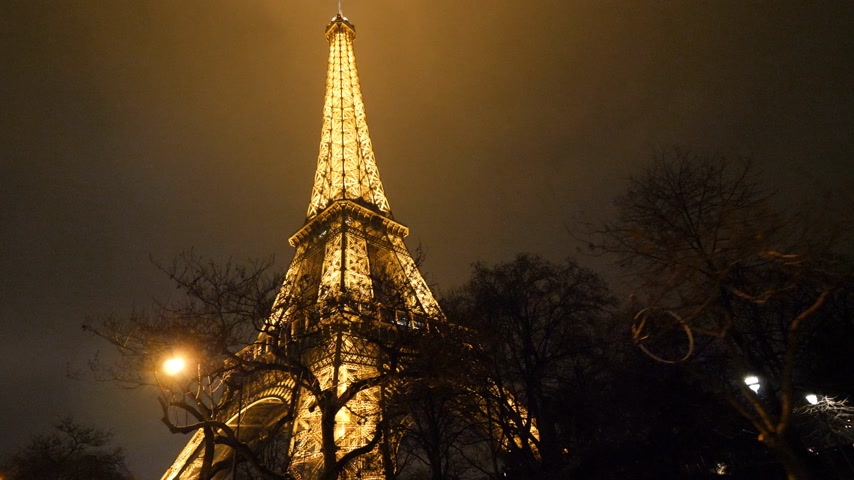 ave : PARIS, FRANCE - JAN 2019: Cinematic Steadicam movement under Eiffel Tower illuminated at night in Paris Stock Footage
