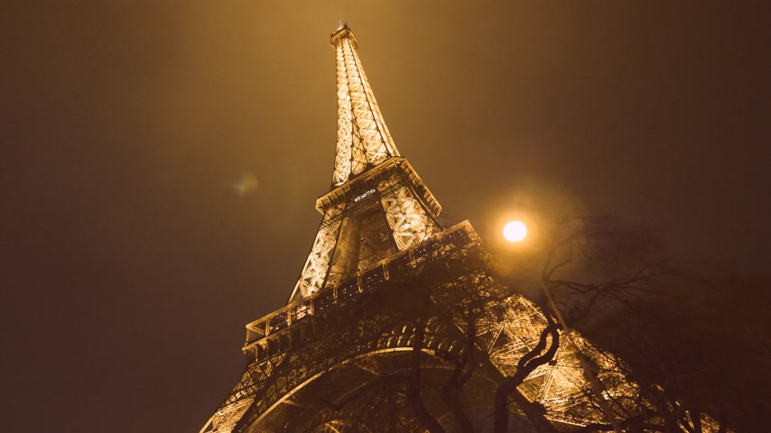 ave : PARIS, FRANCE - JAN 2019: Cinematic motion night twilight illuminated majestic Eiffel Tower down to top view in Paris - the most visited monument in France being lit sightseeing discovering the French capital