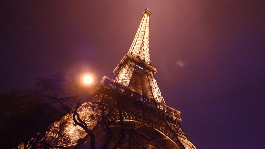 ave : PARIS, FRANCE - JAN 2019: Cinematic motion approaching Eiffel Tower in Paris - night footage of the iconic tourist attraction monument