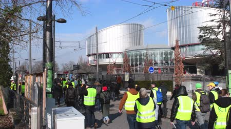 riot : STRASBOURG, FRANCE - FEB 02, 2018: People demonstrating walking in front of European Court of Human Rights during protest of Gilets Jaunes Yellow Vest manifestation anti-government demonstrations Stock Footage