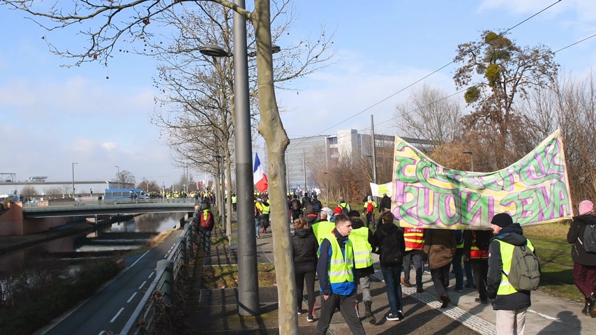 water cannon : STRASBOURG, FRANCE - FEB 02, 2018: People demonstrating walking during protest of Gilets Jaunes Yellow Vest manifestation at European Parliament in Strasbourg protected by Police vans