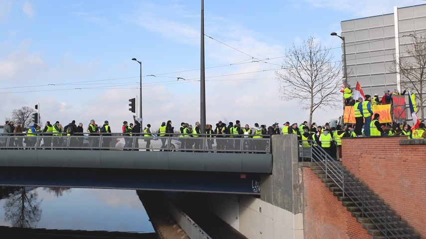 water cannon : STRASBOURG, FRANCE - FEB 02, 2018: People demonstrating on Pont Joseph Bech during protest of Gilets Jaunes Yellow Vest manifestation anti-government demonstrations European Parliament