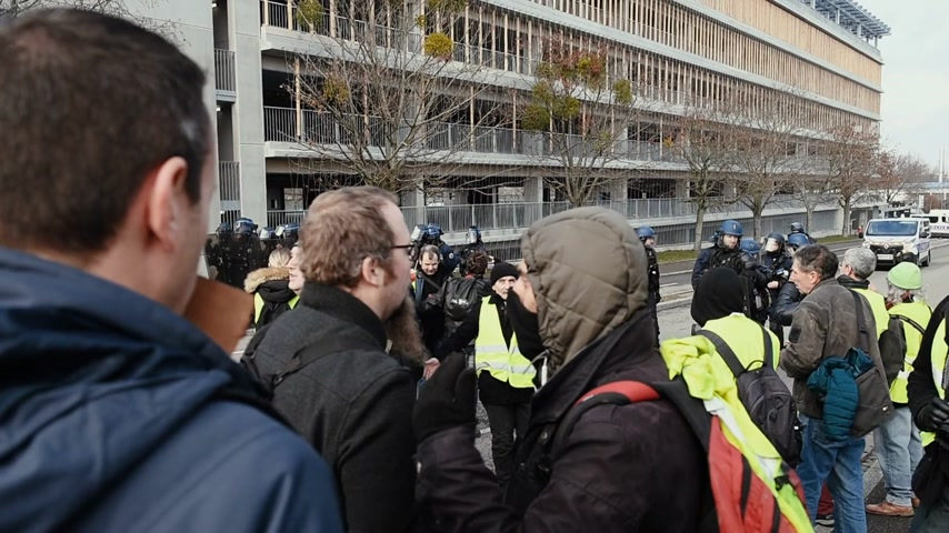 water cannon : STRASBOURG, FRANCE - FEB 02, 2018: Woman addressing to police officers  during protest of Gilets Jaunes Yellow Vest manifestation on the 12 Saturday of anti-government demonstrations