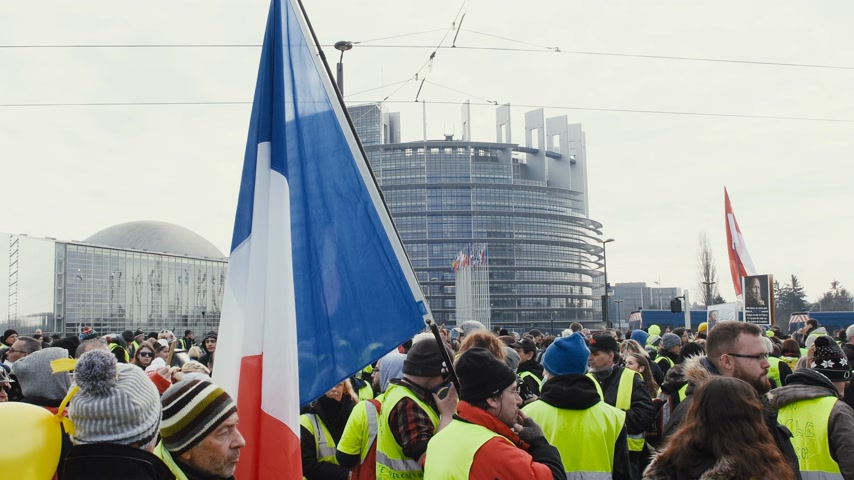 anarchia : STRASBOURG, FRANCE - FEB 02, 2018: People with French flags in front of Parliament during protest of Gilets Jaunes Yellow Vest manifestation on the 12 Saturday of anti-government demonstrations