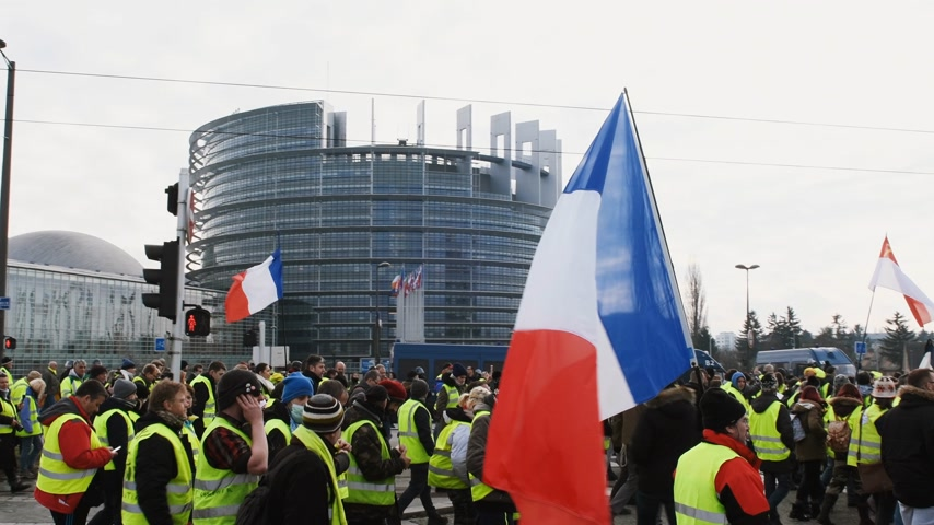 vest : STRASBOURG, FRANCE - FEB 02, 2018: Gilets Jaunes Yellow Vest protesters with French national flag manifestation on the 12 Saturday of anti-government demonstrations European Parliament
