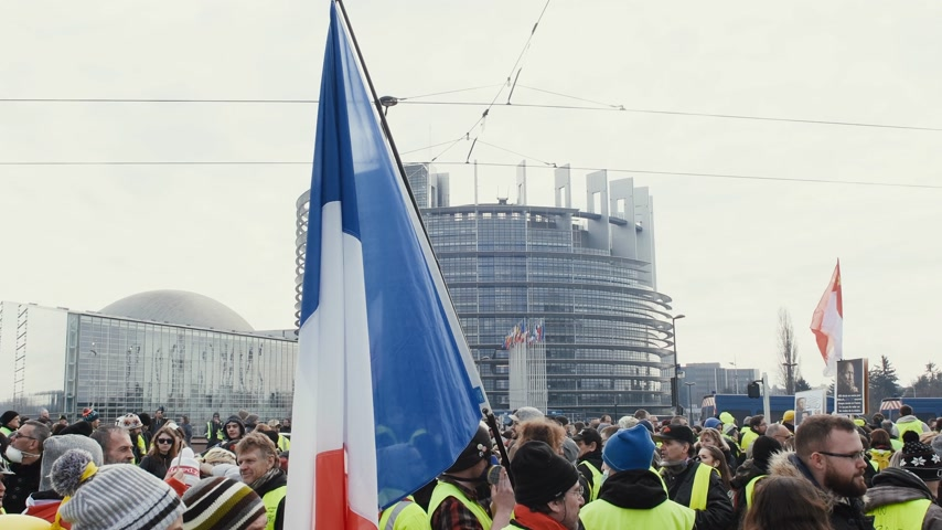 austerity : STRASBOURG, FRANCE - FEB 02, 2018: People with French flags in front of Parliament during protest of Gilets Jaunes Yellow Vest manifestation on the 12 Saturday of anti-government demonstrations