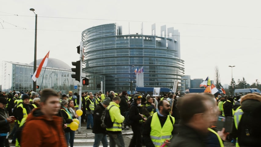 austerity : STRASBOURG, FRANCE - FEB 02, 2018: People walking with anti Emmanuel Macron placards in front of European Parliament demonstrating walking during protest of Gilets Jaunes Yellow Vest manifestation on the 12 Saturday of anti-government demonstrations Stock Footage