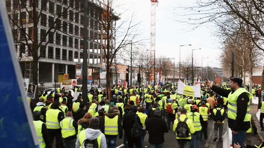 austerity : STRASBOURG, FRANCE - FEB 02, 2018: Elevated view of people demonstrating walking during protest of Gilets Jaunes Yellow Vest manifestation anti-government demonstrations