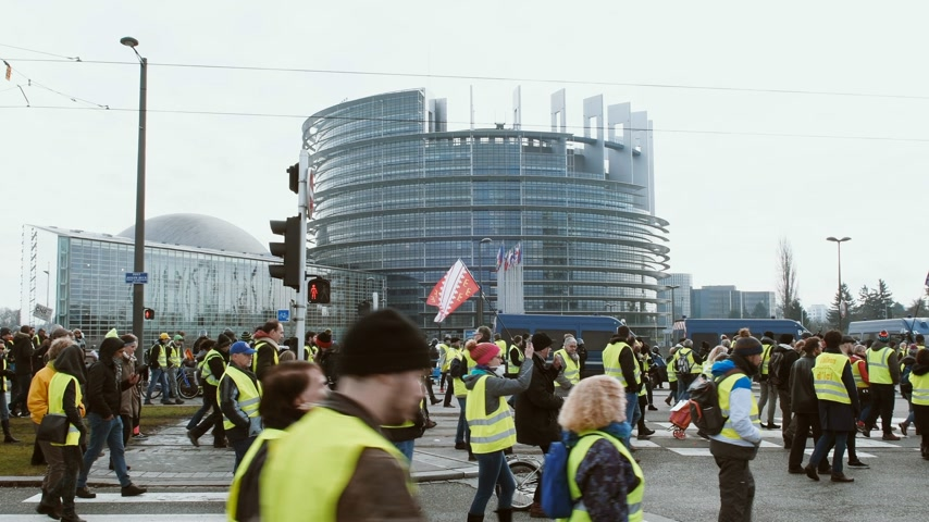 europeu : STRASBOURG, FRANCE - FEB 02, 2018: Large crowd of people Gilets Jaunes Yellow Vest manifestation anti-government demonstrations in Strasbourg in Front of European Parliament
