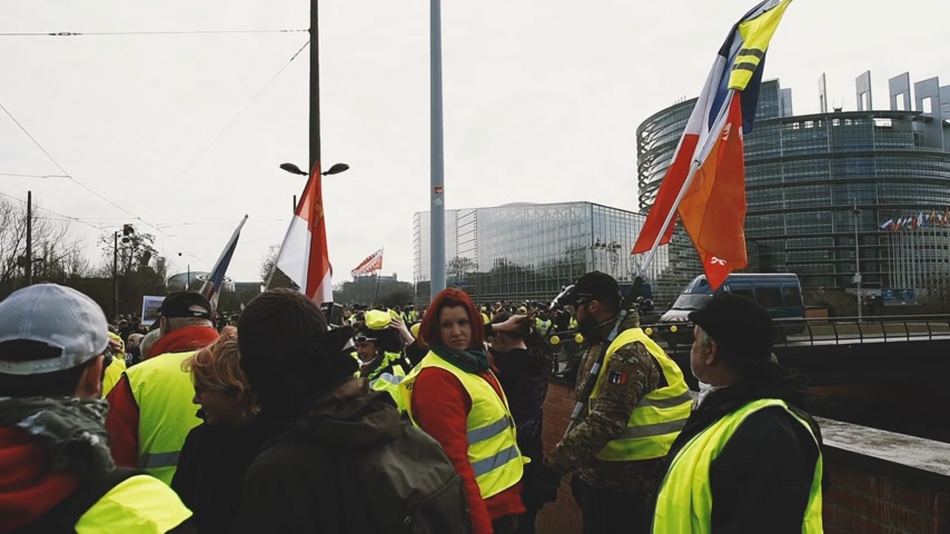 water cannon : STRASBOURG, FRANCE - FEB 02, 2018: People demonstrating in front of European parliament building during protest of Gilets Jaunes Yellow Vest manifestation of anti-government demonstrations