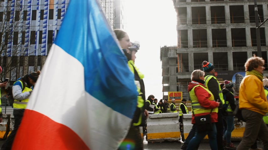 austerity : STRASBOURG, FRANCE - FEB 02, 2018: People demonstrating walking with flags during protest of Gilets Jaunes Yellow Vest manifestation anti-government demonstrations on Boulevard de Dresde Stock Footage