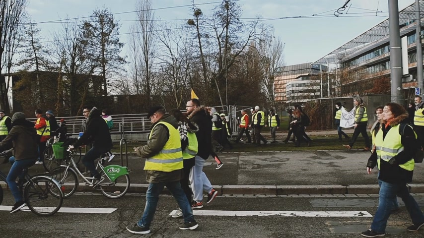 zsaru : STRASBOURG, FRANCE - FEB 02, 2018: Handheld POV walking with crowd at demonstration of Gilets Jaunes Yellow Vest manifestation on the 12 Saturday of anti-government demonstrations Stock mozgókép