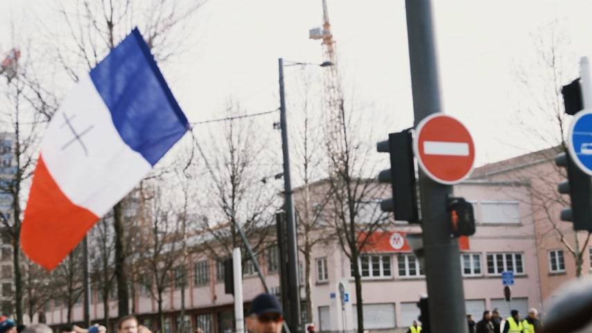 sosyal konular : STRASBOURG, FRANCE - FEB 02, 2018: People demonstrating with French flag with black orthodox cross during protest of Gilets Jaunes Yellow Vest manifestation on the 12 Saturday of anti-government demonstrations Stok Video