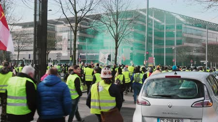 grenade : STRASBOURG, FRANCE - FEB 02, 2018: People demonstrating in front of Maison de la Region Grand Est - Gilets Jaunes Yellow Vest manifestation on the 12 Saturday of anti-government demonstrations Stock Footage