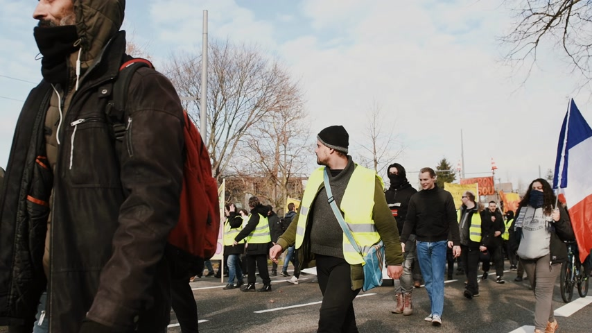 austerity : STRASBOURG, FRANCE - FEB 02, 2018: Large crowd of people demonstrating walking peacefully with anti-Macron placards protest of Gilets Jaunes Yellow Vest manifestation on the 12 Saturday of anti-government demonstrations Stock Footage