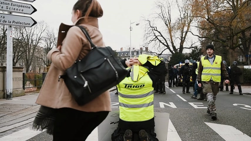 анти : STRASBOURG, FRANCE - FEB 02, 2018: Gilets Jaunes Yellow Vest manifestation with man kneeling in front of police squadron on the 12 Saturday of anti-government demonstrations Стоковые видеозаписи