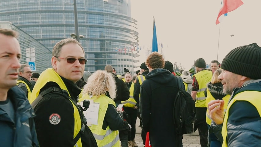sztrájk : STRASBOURG, FRANCE - FEB 02, 2018: Police and protestors in front of European Parliament - people demonstrating walking during protest of Gilets Jaunes Yellow Vest anti-government demonstrations Stock mozgókép