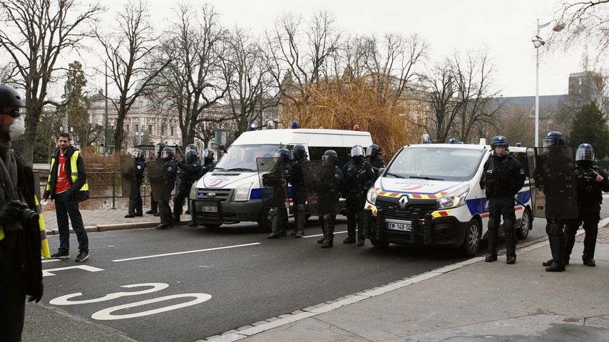austerity : STRASBOURG, FRANCE - FEB 02, 2018: Police officers protecting street from people demonstrating walking during protest of Gilets Jaunes Yellow Vest manifestation on the 12 Saturday of anti-government demonstrations Stock Footage