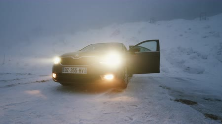 xenon lights : MUMMELSEE, GERMANY - CIRCA 2019: Woman preparing heating lonely parked Skoda Octavia brown car in snowy storm parking in German Alps Black Forest mountains heavy snow storm cinematic footage Stock Footage