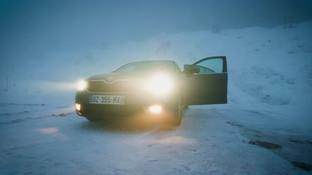xenon lights : MUMMELSEE, GERMANY - CIRCA 2019: Woman approaching heating lonely parked Skoda Octavia brown car in snowy storm parking in German Alps Black Forest mountains heavy snow storm cinematic footage