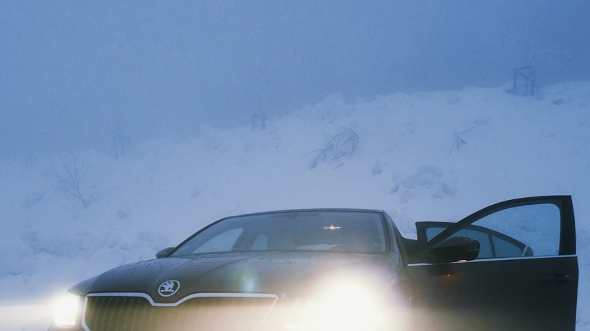 seasons changing : MUMMELSEE, GERMANY - CIRCA 2019: Woman heating lonely parked Skoda Octavia brown car in snowy storm parking in German Alps Black Forest mountains Stock Footage