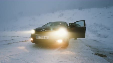 auto parking : MUMMELSEE, GERMANY - CIRCA 2019: Woman preparing heating lonely parked Skoda Octavia brown car in snowy storm parking in German Alps Black Forest mountains heavy snow storm
