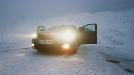 xenon lights : MUMMELSEE, GERMANY - CIRCA 2019: Woman lonely parked Skoda Octavia brown car in snowy storm parking in German Alps Black Forest mountains heavy snow storm