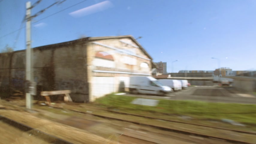 departing : View from the train window over the nearby highway with trucks cars view from the high speed window of an ultra-fast train in France with destination Eurotunnel Channel tunnel London Stock Footage