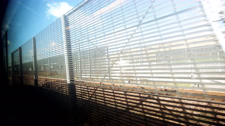 departing : Approaching the Eurotunnel Getlink fast view from train Eurostar window with security fences along the path
