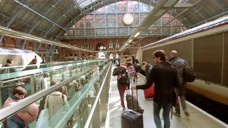 victorian : LONDON, UNITED KINGDOM - CIRCA 2019: Commuters people walking near Eurostar fast train in St Pancras International station platform - perspective view