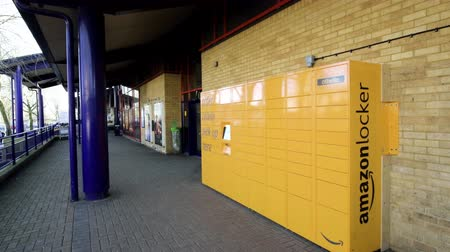 zelfbeeld : LONDON, UNITED KINGDOM - CIRCA 2019: Side view of Amazon locker orange delivery package locker in the University Campus - Amazon Locker self-service parcel delivery service offered by online retailer Amazon.com.- Stockvideo