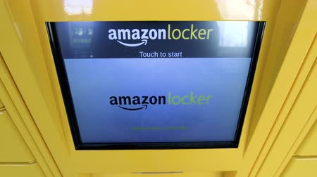locker : LONDON, UNITED KINGDOM - CIRCA 2017: POV at the display monitor of Amazon locker orange delivery package touch to start - Amazon Locker self-service parcel delivery service offered by online retailer Amazon.com.- Stock Footage
