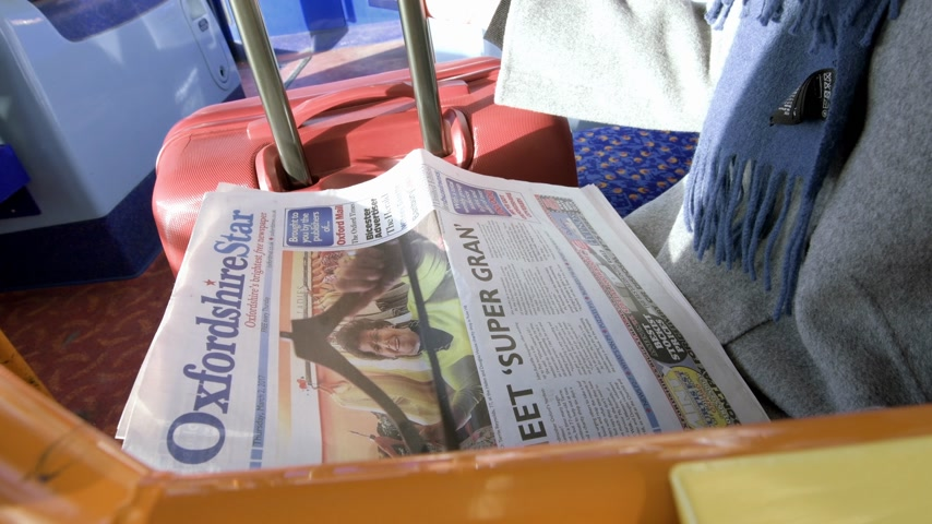 inside bus : OXFORD, UNITED KINGDOM - CIRCA 2019: Young female student inside double decker bus reading Oxfordshire Star newspaper motion inside commuting in Oxford