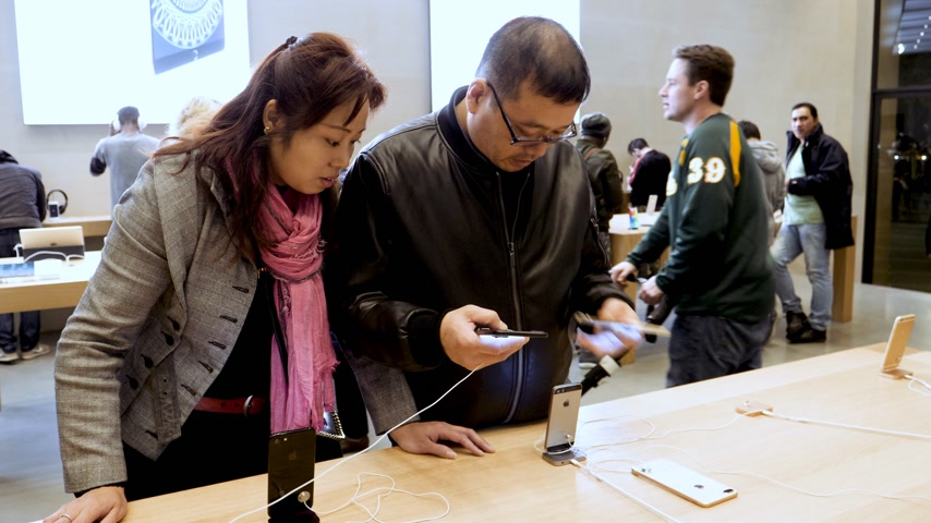 latest : BARCELONA, SPAIN - CIRCA 2019: Chinese Asian customers people inside Apple Store Passeig de Gracia admiring latest smartphones iPhone technology gadgets by Cupertino giant Apple Computers Stock Footage