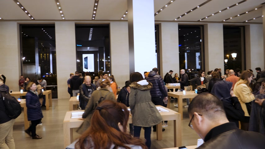 macintosh : BARCELONA, SPAIN - CIRCA 2019: Pan over large crowd of customers people inside Apple Store Passeig de Gracia admiring latest technology gadgets by Cupertino giant Apple Computers